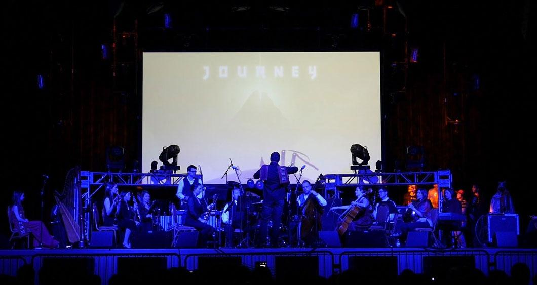 Fifth House Ensemble in front of a screen projection of Journey