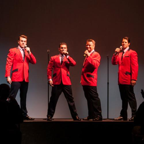 Jersey Boys cast members performing in red jackets