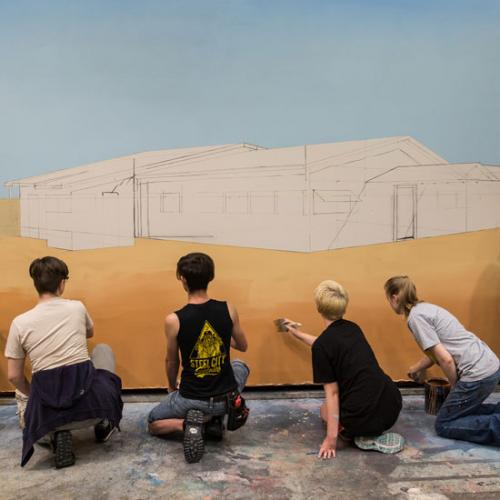 Four Students Painting a Backdrop