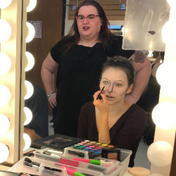 Allison Lowery overseeing a student putting on makeup